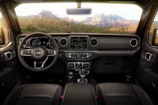 Interior of the 2021 Jeep® Wrangler Sahara 4xe includes standard 7-inch Uconnect screen.